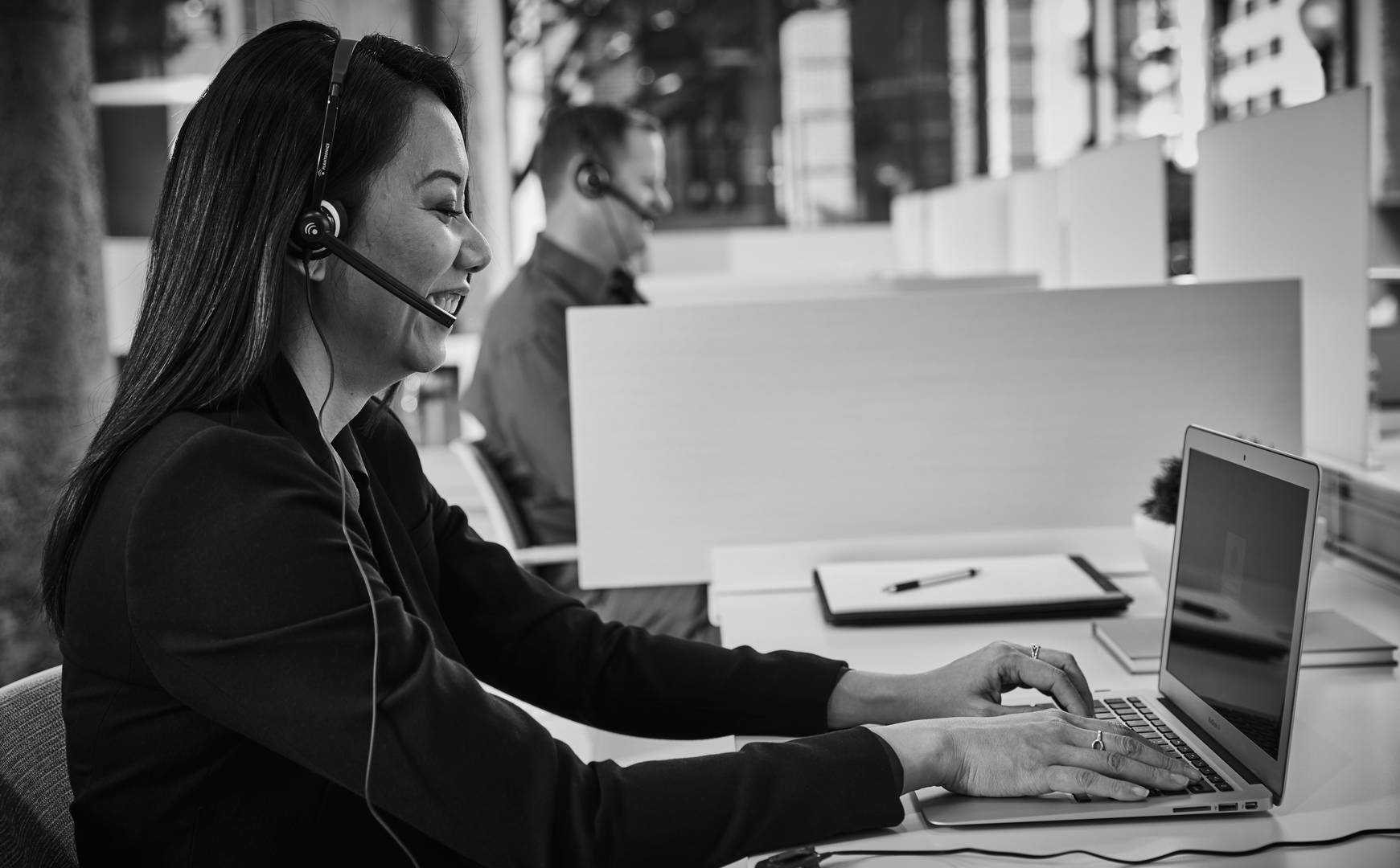 A customer service representative talks on a headset while typing at a computer
