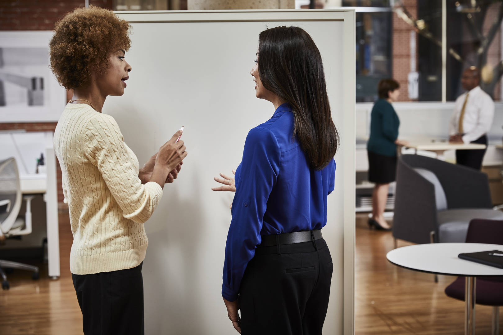 Two women working at a whiteboard