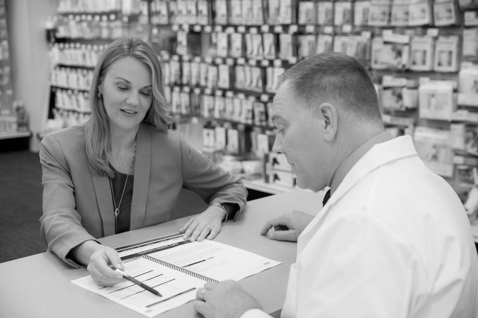 A Good Neighbor Pharmacy business coach reviews performance reports with a pharmacist