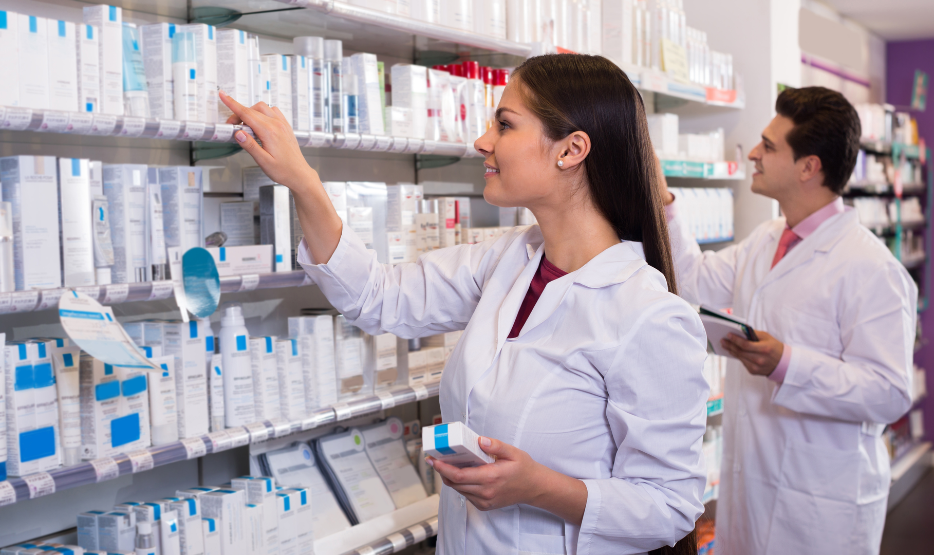 Two pharmacists filling prescriptions in a pharmacy