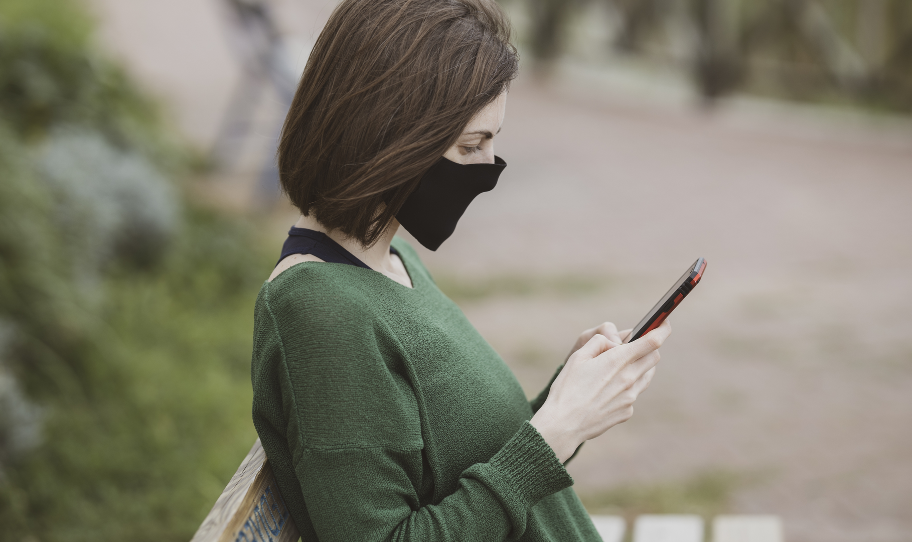 A woman wearing a face mask reading a text message from her pharmacist on her phone