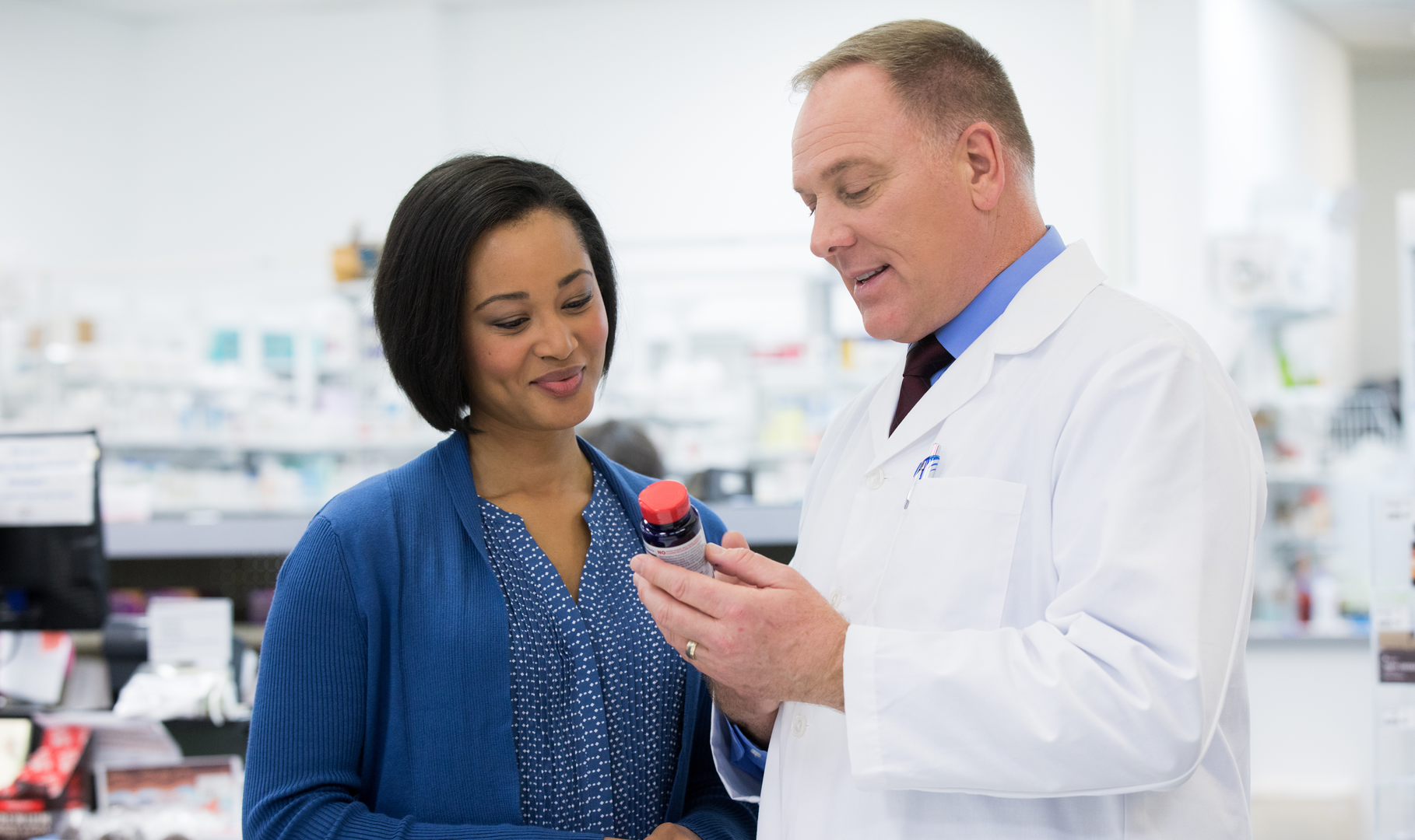 A pharmacist educating a patient on vitamin supplements