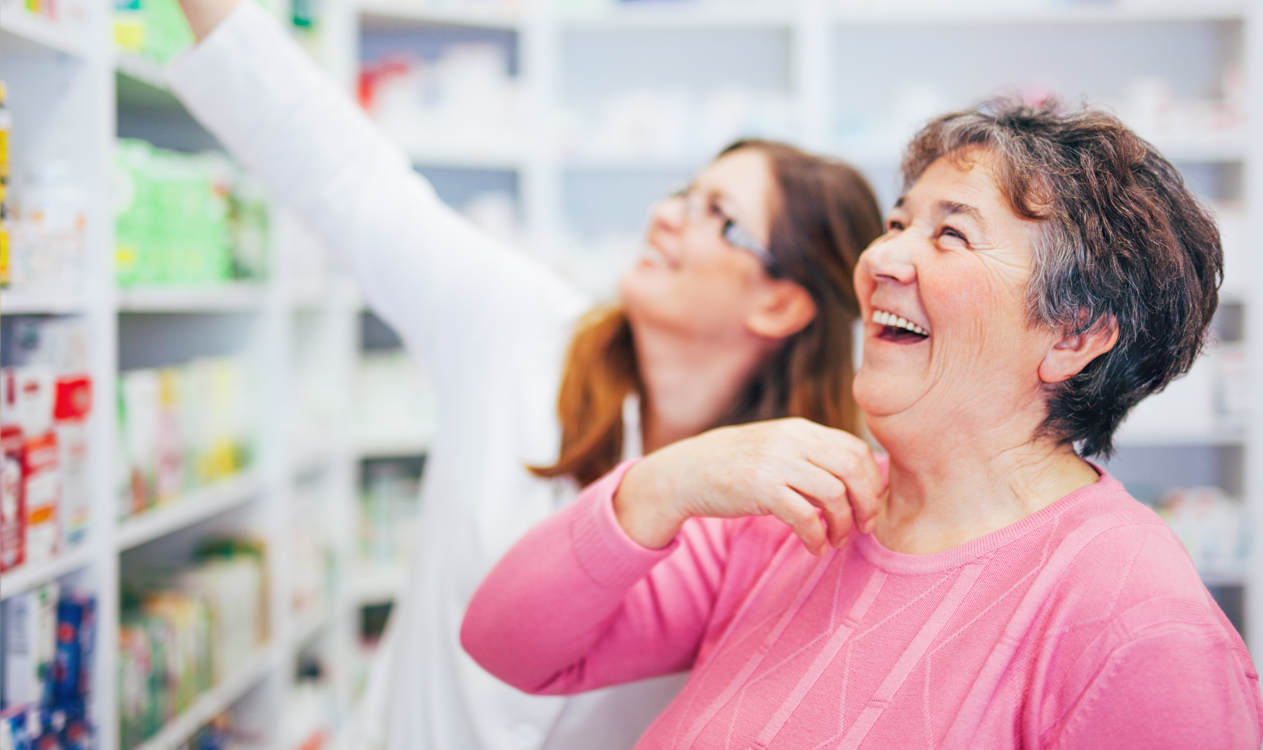 A customer laughing joyfully as a pharmacist helps her find the medication she needs