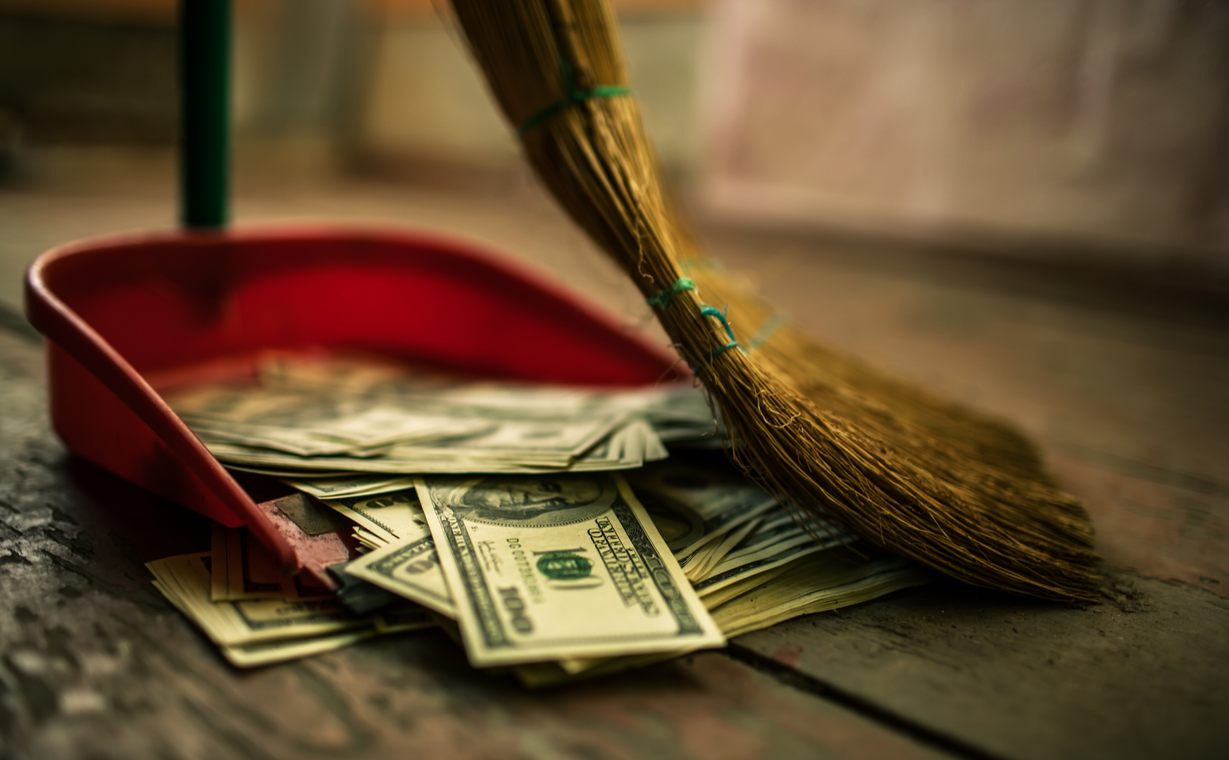Someone using a broom to sweep dollar bills into a dust pan