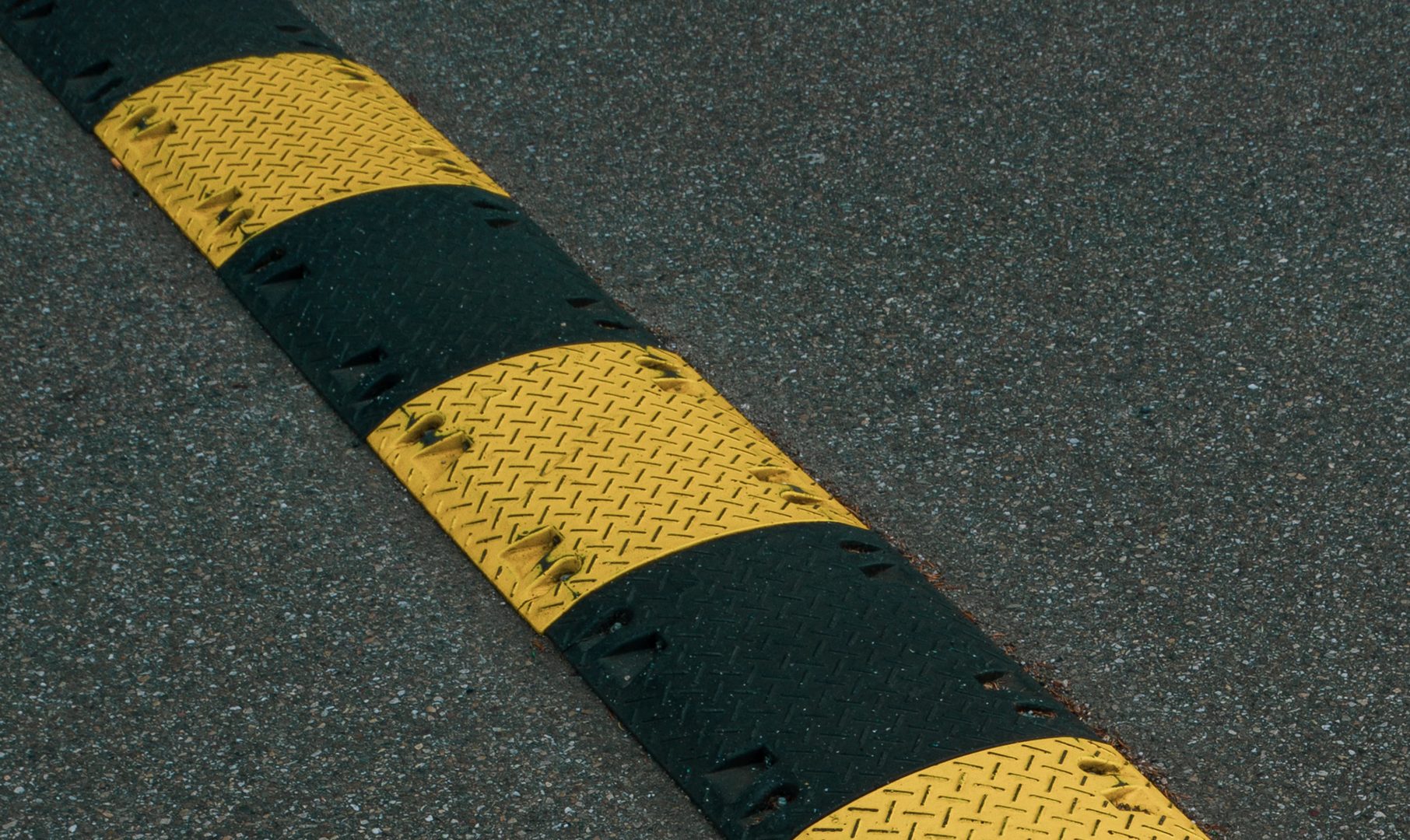 A yellow and black striped speed bump on asphalt