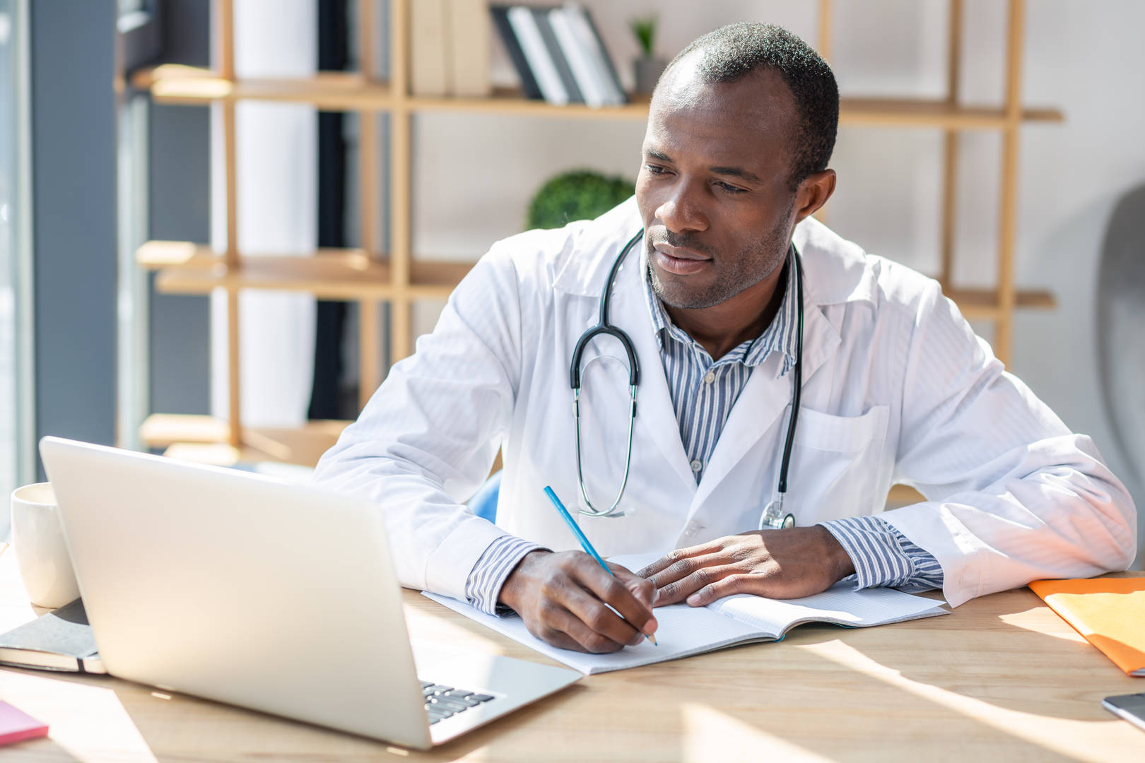 Physician looks at laptop and takes notes
