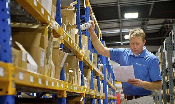 MWI Animal Health employee in blue shirt pulling a product in a warehouse