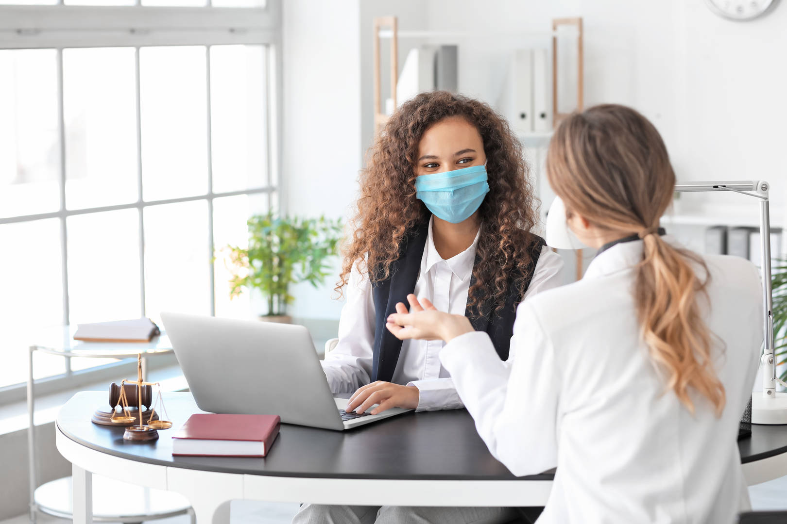 2 healthcare professionals wearing face masks and talking over laptop